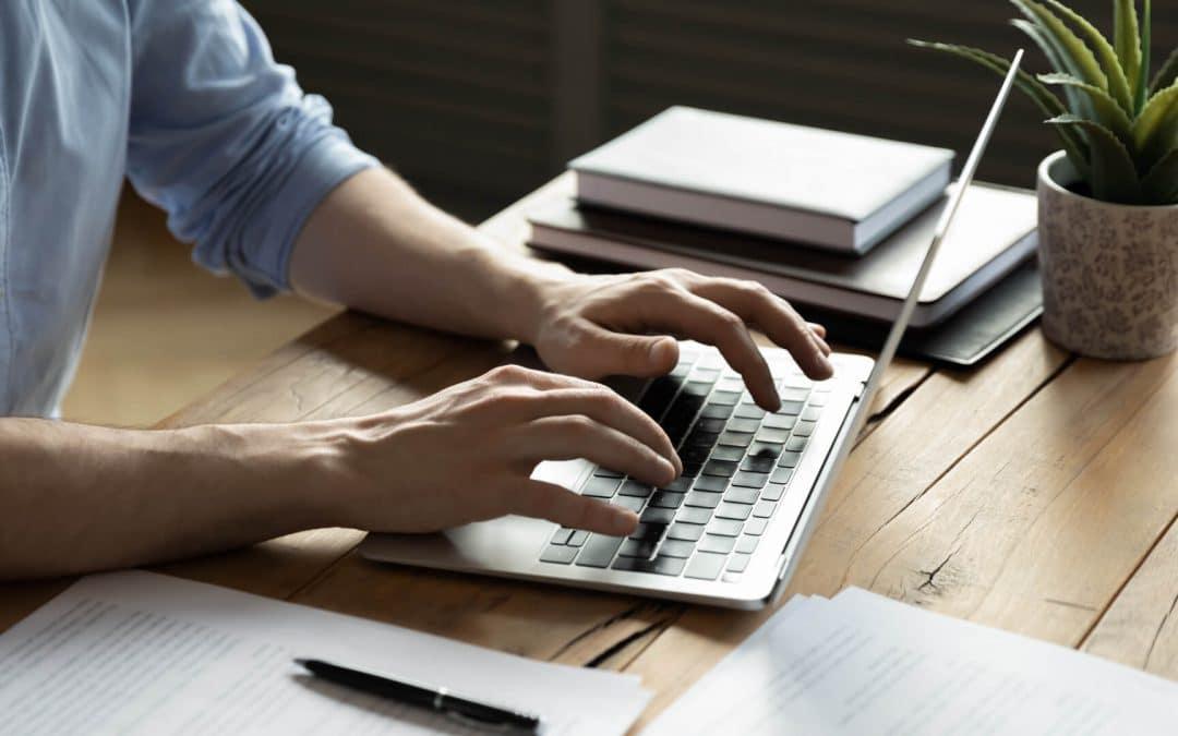 Persoon die op zijn laptop webteksten aan het schrijven is